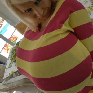 Yellow and pink striped sweater streatched by heavy breasts