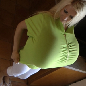 Pumped up mega breasts in a green shirt zipped up tight