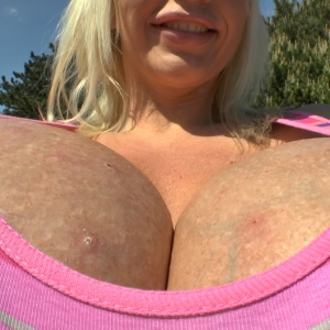 Mega gigantic breasts stretching out a pink striped tight shirt